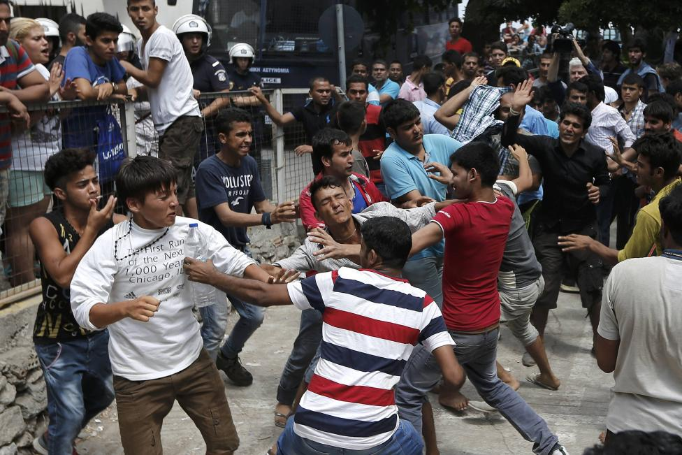 Pakistani, Iranian and Afghani migrants scuffle outside the police station of the city of Kos
